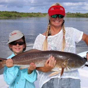 family with redfish on charter